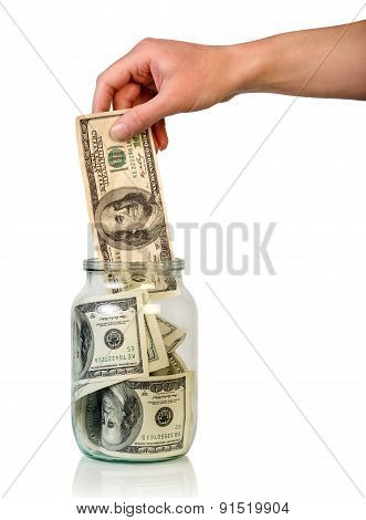 Hand puts money in jar