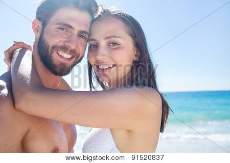 Happy couple hugging and smiling at camera at the beach