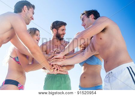 Group of friends standing in circle hands together at the beach