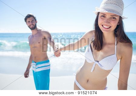 Smiling couple holding hands and looking at camera at the beach