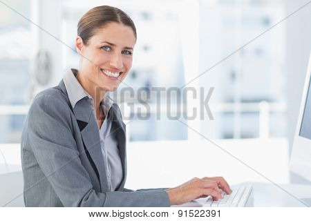 Smiling businesswoman using computer in office