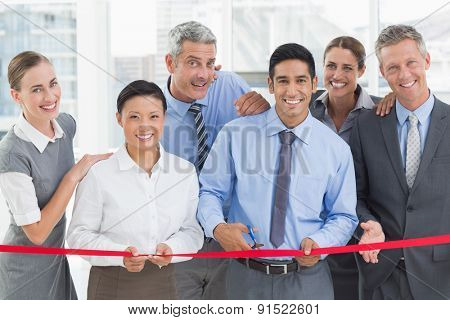 Business man cutting red strip in office