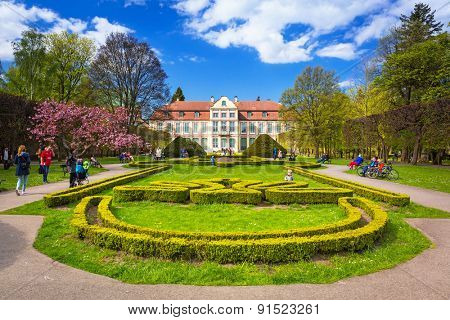 GDANSK, POLAND - MAY 3, 2015: People in the gardens at Abbots Palace in Gdansk. This roccoco palace in Gdansk Oliwa was constructed in the 15th century and is a big tourist attraction.
