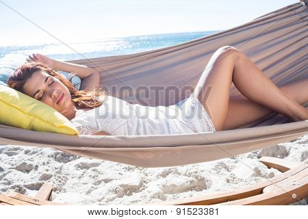 Brunette relaxing in the hammock at the beach