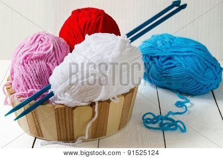 Skeins Of Yarn And Knitting Needles In A Basket
