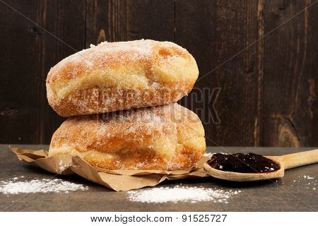 Jelly donuts with spoon of jam against dark wood