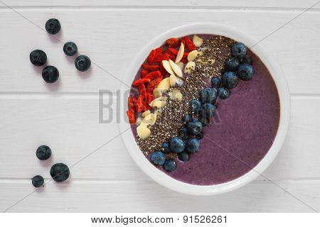 Blueberry smoothie bowl on white wood