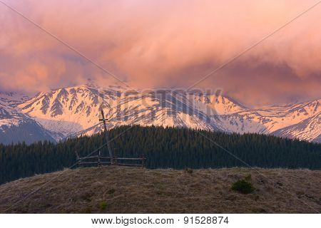 Spring in the mountains. Beautiful sunrise. Wooden cross on a hill