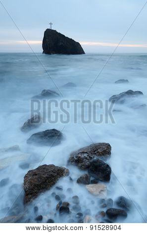 Cross on the rock. Sea landscape