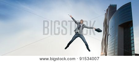 Businessman Jumping In Joy. Full Length Of Smart Happy Man Holding Briefcase In The Air. Outdoors