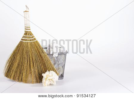 besom and wastebasket with white waste paper and paper ball