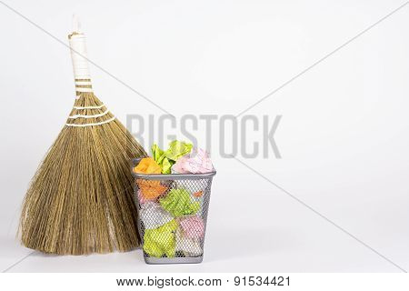 isolated besom and wastebasket with color waste paper