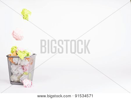isolated wastebasket full of waste paper and fly ball