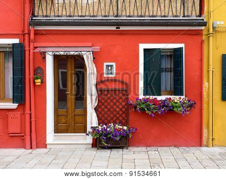 Burano, Italy - 21 May 2015: Red Painted Building. One Of The Many Different Coloured Painted Buildi