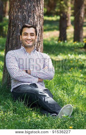 Smile Young Gorgeous Man Sitting On Meadow In A Park. Happy Guy In Forest