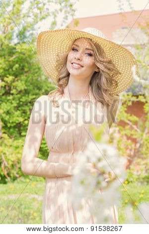 bright beautiful young happy woman walks through the park near a flowering tree on a sunny day