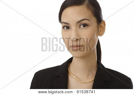 Closeup portrait of beautiful young Asian businesswoman, looking at camera.
