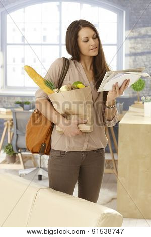 Young woman arriving at home, checking mail, holding shopping bag.