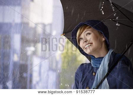 Portrait of beautiful young woman holding umbrella in rain, looking up, smiling.