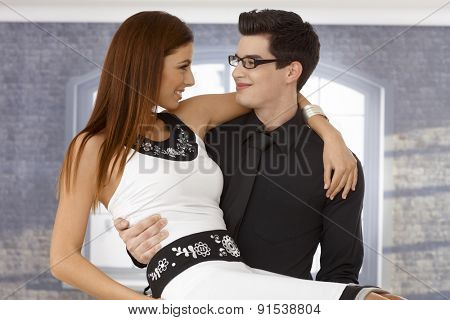 Young man holding girlfriend in arms, hugging, looking affectionate.