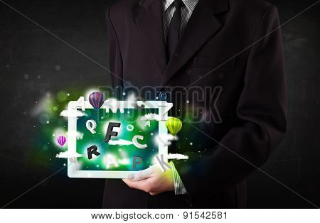 Young person showing white tablet with abstract letters and sky