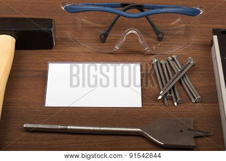 Welding goggles with badge and nails on table