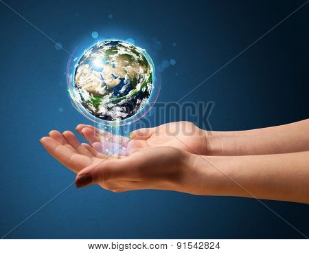 Young woman holding in her hand a glowing earth globe, Elements of this image furnished by NASA