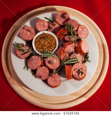 sliced sausages on a plate with rosemary and pepper