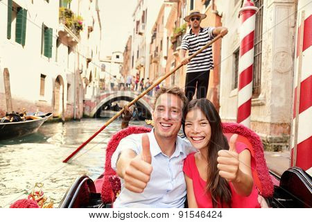 Tourists happy couple traveling in Venice gondola giving thumbs up hand sign joyful on travel. Romantic young beautiful couple on vacation holidays sailing in venetian canal in gondole. Italy