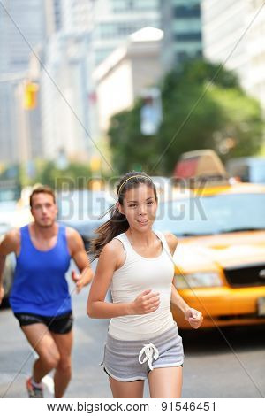 Running workout in New York City. Urban runners people jogging in busy street in New York NYC. Young adults asian caucasian jogging in traffic on Manhattan during summer training for Marathon.