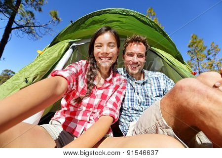 Selfie camping people in tent taking self portrait using camera smartphone. Couple of campers taking picture smiling happy outdoors in forest. Happy people having fun. Asian woman, Caucasian man.