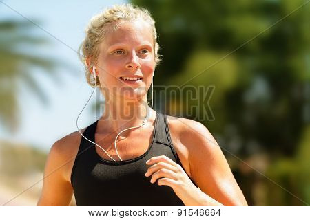 Running woman sweating workout with earphones. Female runner listening to music in earbuds. Girl athlete jogging city with palm trees. Healthy lifestyle concept with young blonde fitness model.