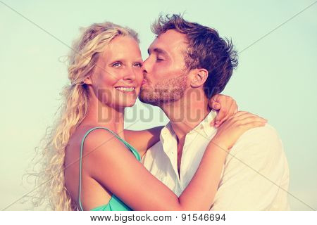 Romantic couple kissing in love enjoying sunset at beach. Young happy man kissing woman on cheek in romance on summer beach during honeymoon vacation holidays travel.