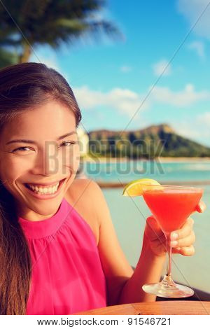 Woman drinking alcohol drinks cocktail at beach bar resort in Waikiki, Honolulu city, Oahu, Hawaii, USA. Asian girl tourist looking at camera toasting a glass of strawberry Hawaiian drink at sunset.
