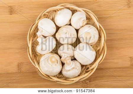 Basket Wicker With Raw Champignons On Bamboo Board