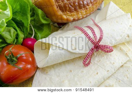 Wrapped Empty Tortillas On A Table With Tomato, Lettuce And Ham