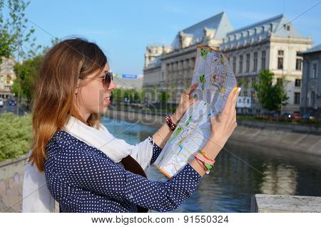 Young Girl Reading A Map Close To A River