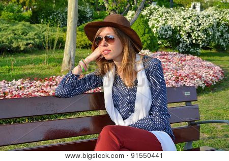 Pensive Girl Sitting On A Park Bench