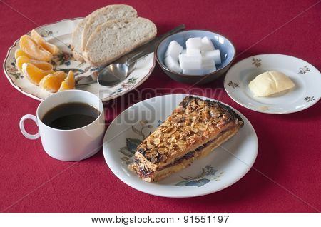 Breakfast set with cake, coffee, bread, butter and orange wedges