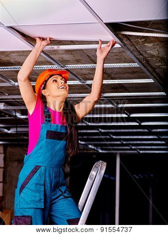 Woman in builder hardhat and uniform installing suspended ceiling
