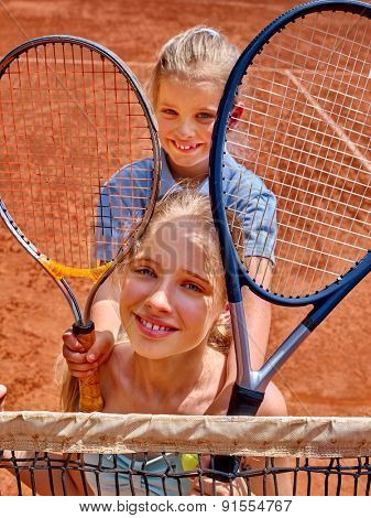 Two sister girl athlete  with racket and ball on  brown tennis court.