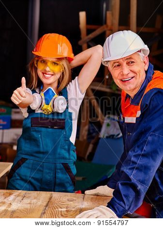 Happy woman and young woman  in builder uniform thumb up.