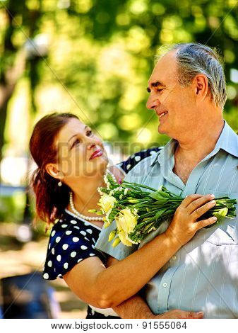 Happy old couple with flower in park summer outdoor.