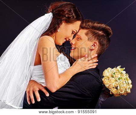 Groom kissing bride . Wedding on black background.