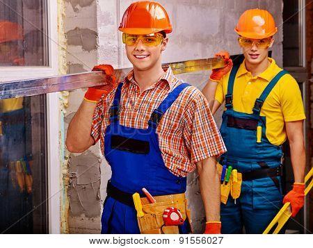 Two handsome men in builder uniform indoor.
