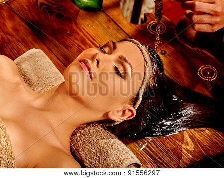 Young woman having head oil Ayurveda spa treatment.