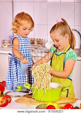 Children  cooking and eating spaghetti at kitchen.
