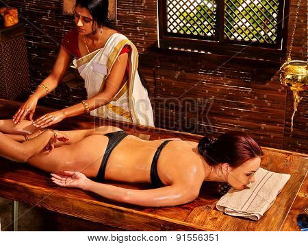 Young woman having leg Ayurveda spa treatment.