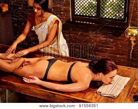 Young woman having leg Ayurveda spa treatment.