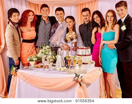 Group guests at wedding table with cake. In the center of bride and groom